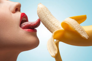 A face of porn star licking a half-peeled yellow banana