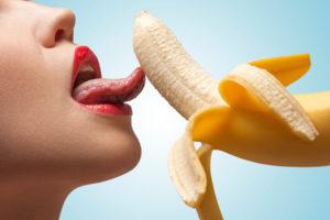 A face of porn star licking a half-peeled yellow banana